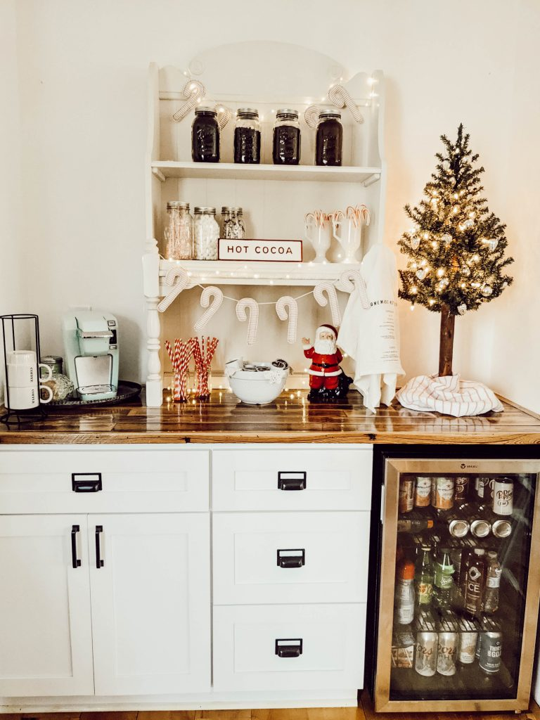 farmhouse coffee bar with white shaker cabinets, built in beverage cooler, and wood countertops