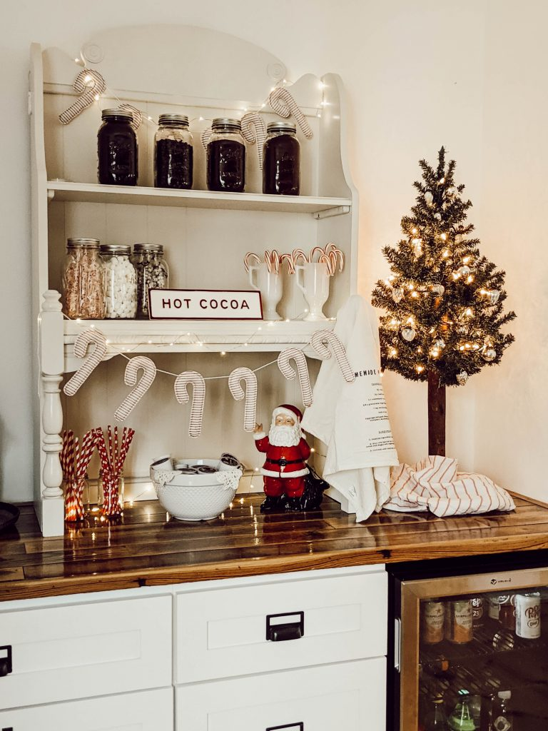 mini rustic glam christmas tree atop built-in coffee bar counters