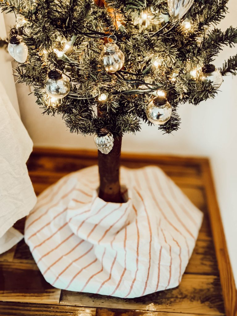mini rustic glam christmas tree with vintage inspired silver ornaments and simple red striped tree skirt