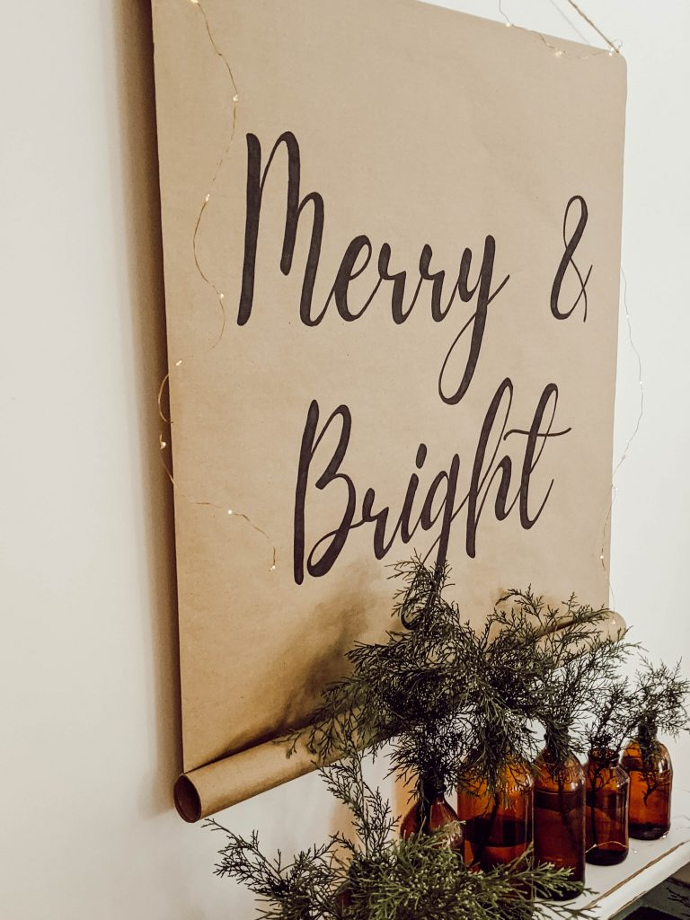 craft paper scroll sign that says Merry and Bright