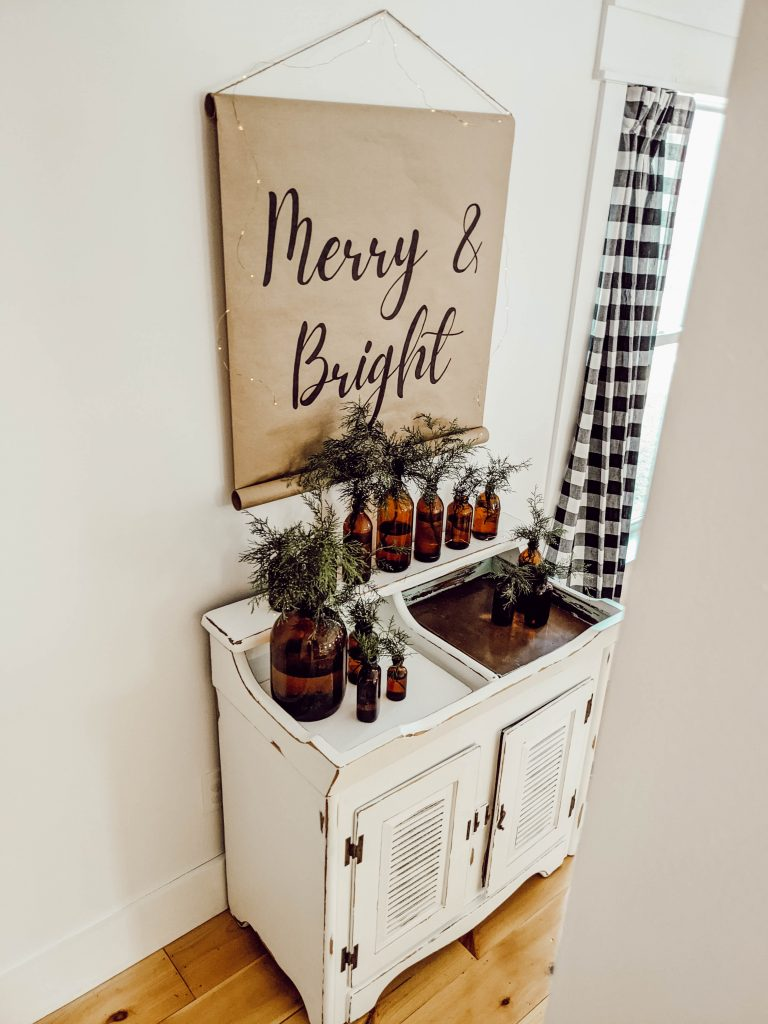 neutral Christmas vignette with farmhouse scroll sign, dry sink, and brown glass bottle collection