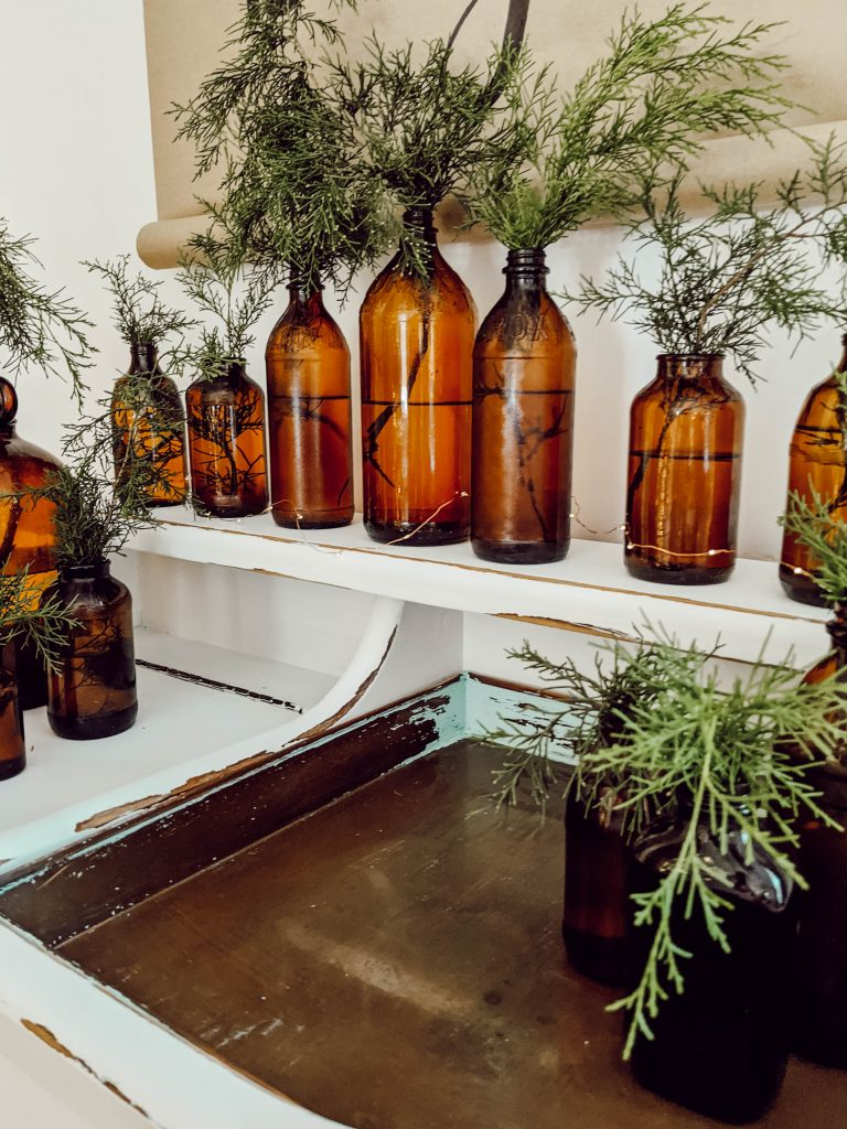collection of vintage amber glass bottles with real cedar greens