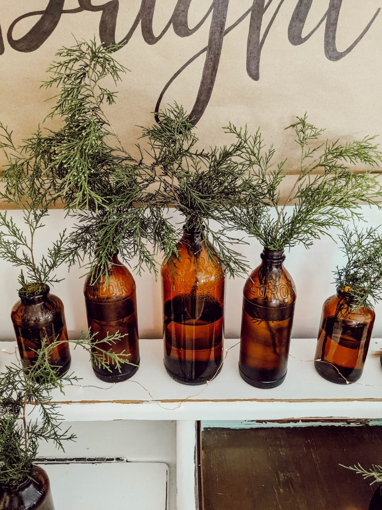 vintage 1940's and 1950's amber glass Clorox bottles with winter greenery