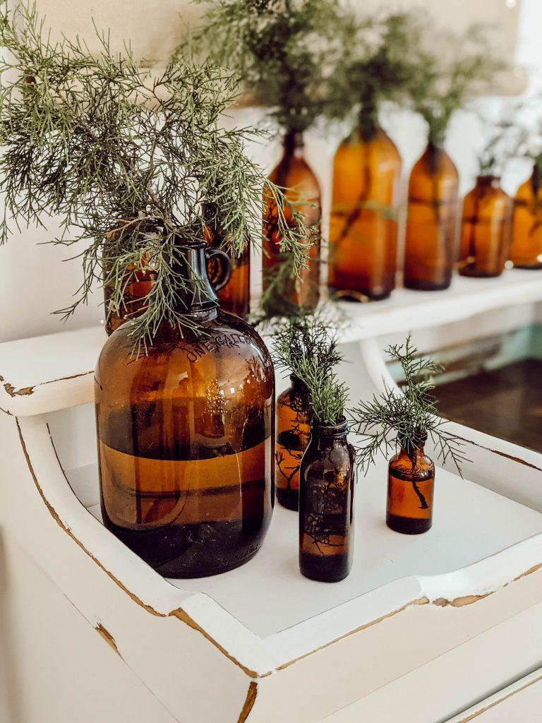 one gallon amber glass jug with fresh cedar greenery