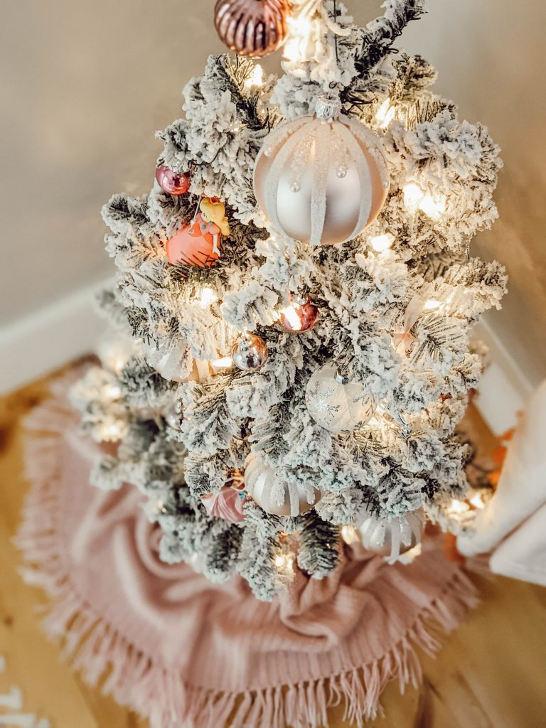 pretty pink ornaments on flocked mini tree with pink fringe tree skirt
