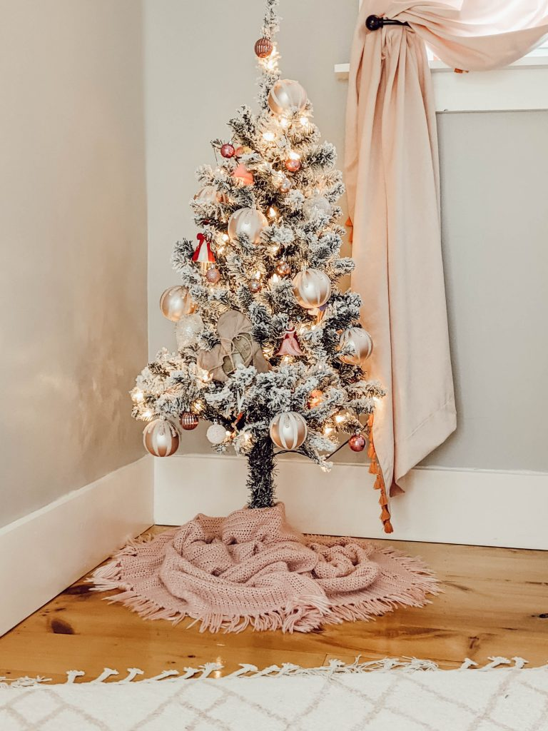 dainty pink ornaments on flocked mini tree with pink fringe tree skirt