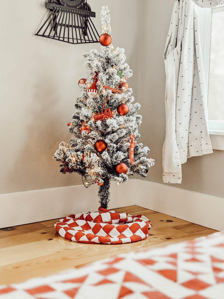 mini flocked Christmas tree with red ornaments and red checkered tree skirt