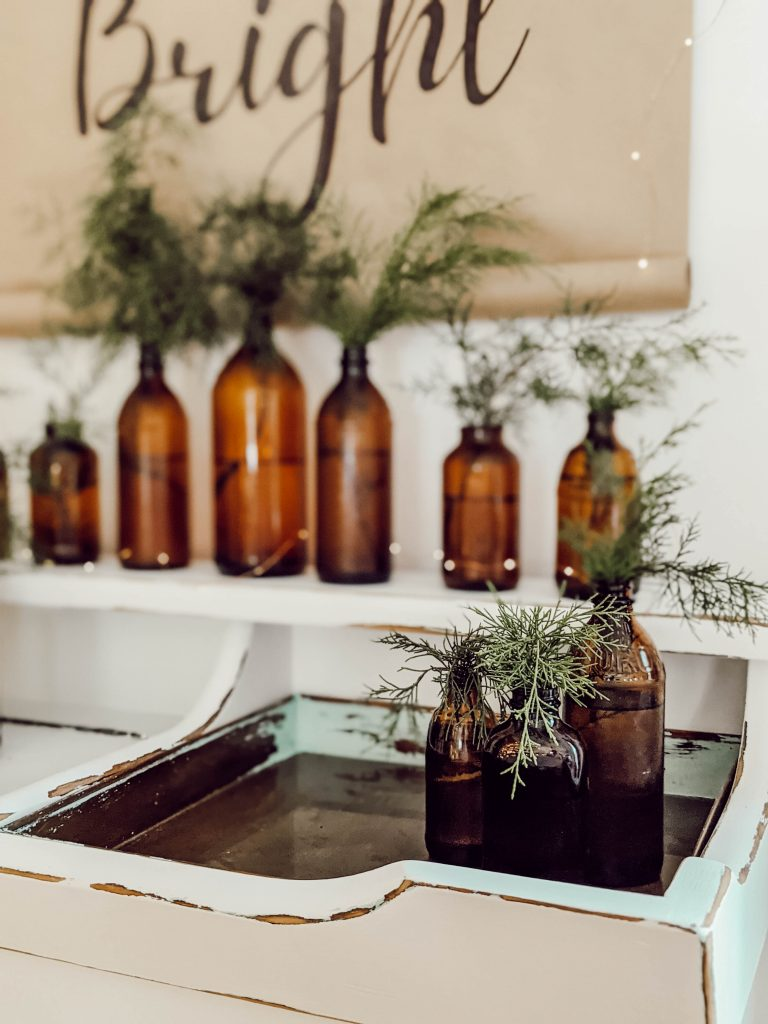 simple holiday decor using brown glass bottles and fresh greenery